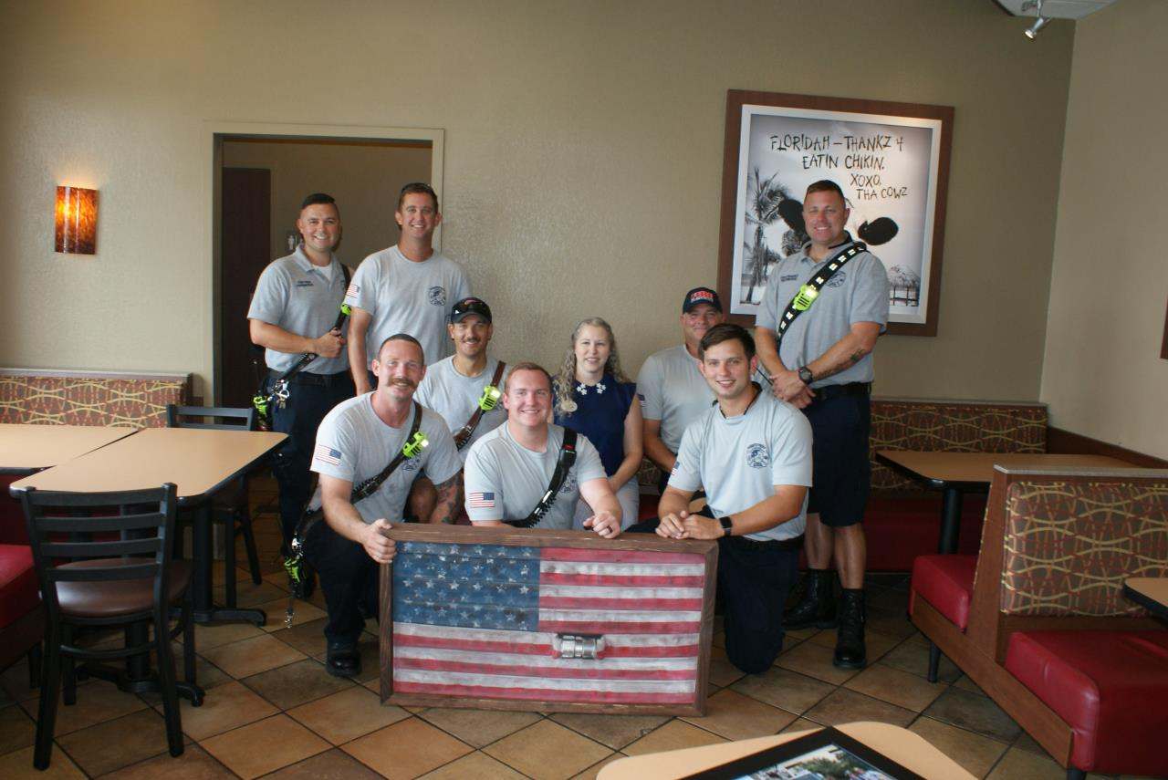 Group of male firefighters posed with Chick-fil-A managing partner and a flag they are presenting to Chick-fil-A made from recycled fire hose.