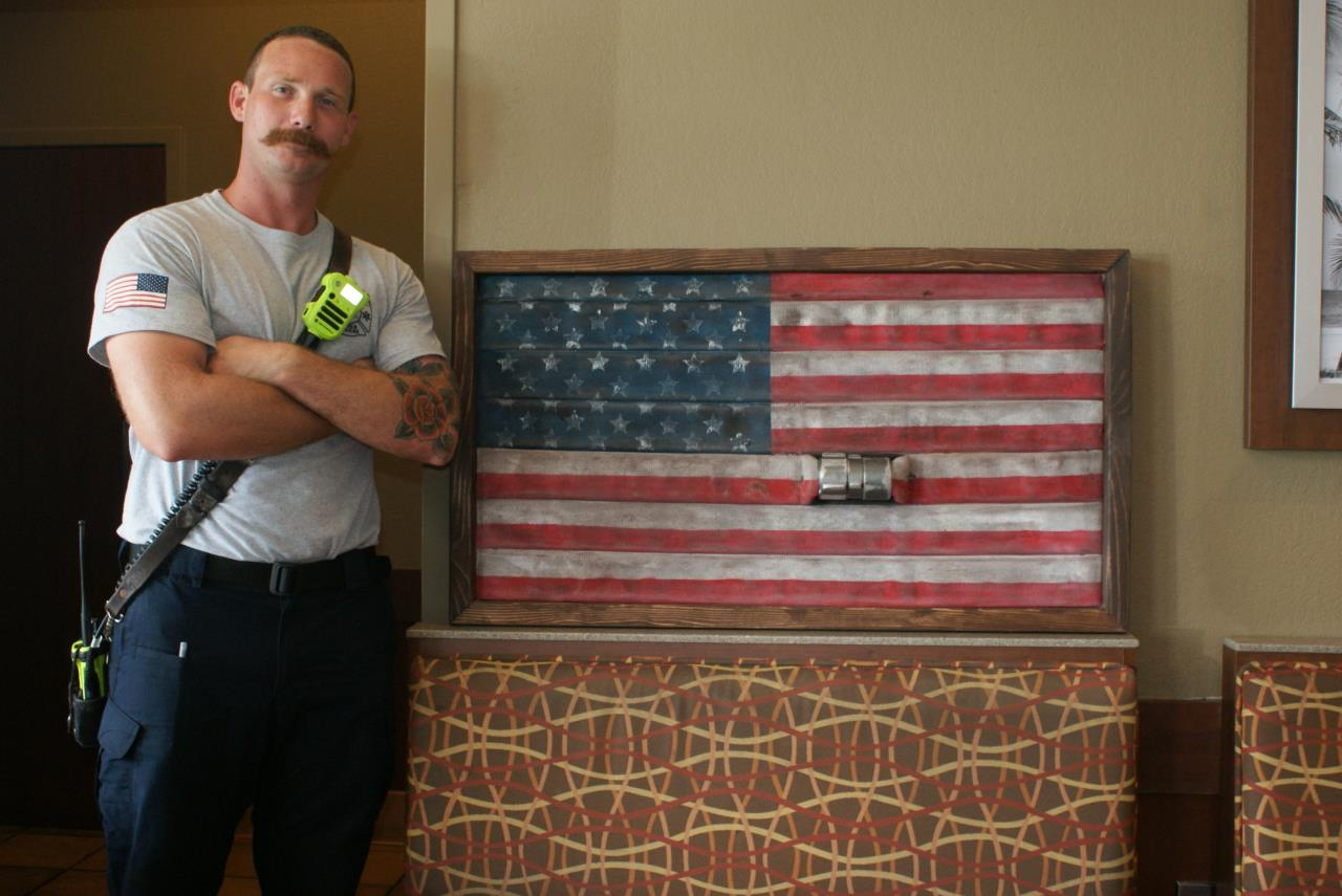 Firefighter Daryl Paul with his arms crossed pictured with a red white and blue flag he made from firehose.